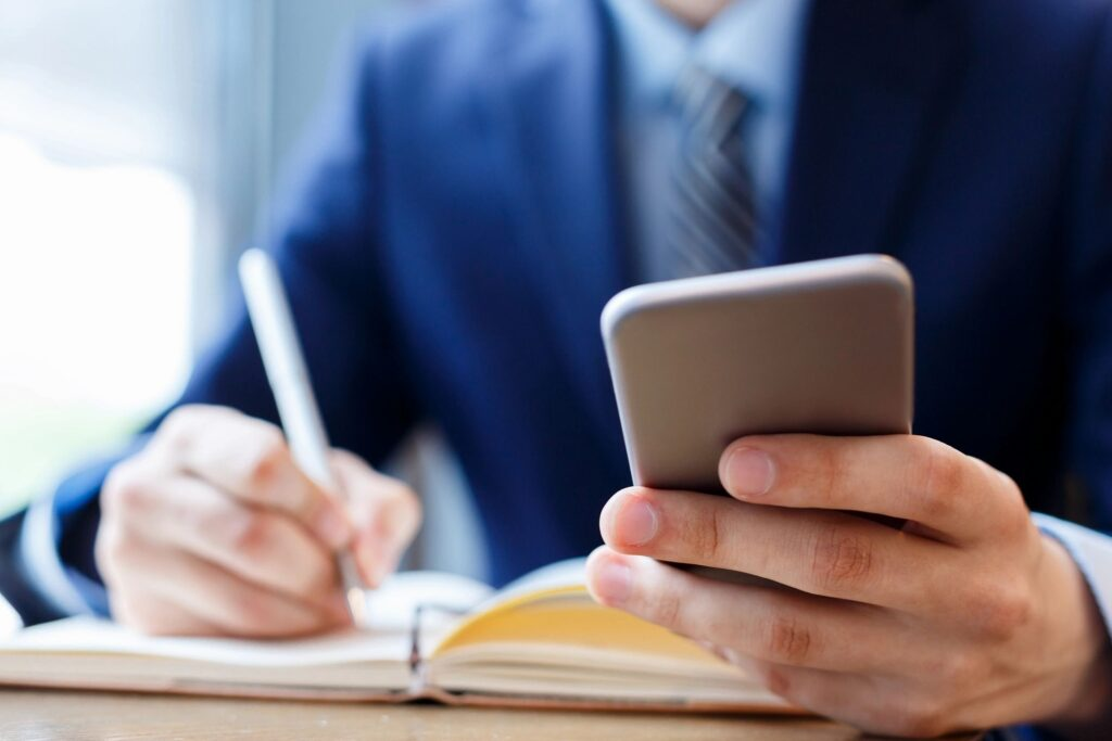 Image of a business man using his phone conducting budgeting and forecasting, courtesy of BDI.